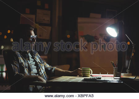 Businessman working at night - Stock Photo