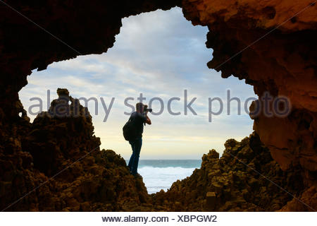 Man taking a photograph at Venus Bay, Australia - Stock Photo