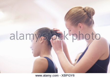 Teenage ballerina helping friend with hair - Stock Photo