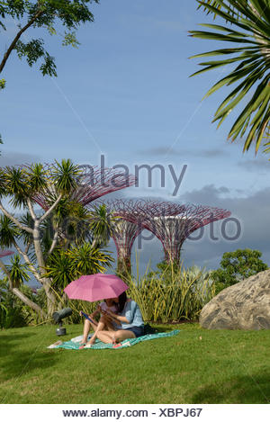 Singapore, Mother and daughter (2-3) relaxing under parasol in garden - Stock Photo