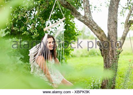 Sweden, Varmland, Filipstad, Gasborn, Horrsjon, Portrait of woman in hammock - Stock Photo