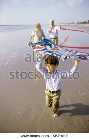 Child flying a kite on the beach with his grandparents - Stock Photo