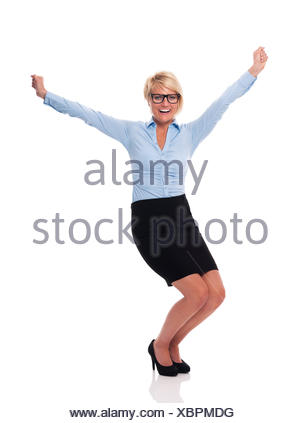 Excited young businesswoman with hands raised, Debica, Poland - Stock Photo