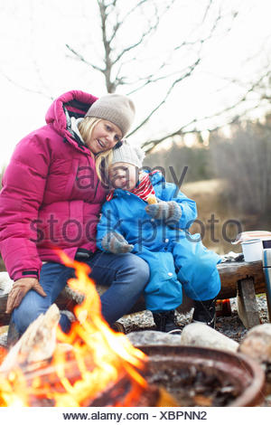 Sweden, Sodermanland, Jarna, Mother with son (2-3) sitting on log by campfire - Stock Photo