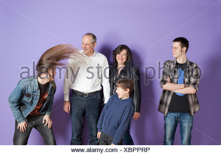 Family watching son headbang in front of purple background - Stock Photo