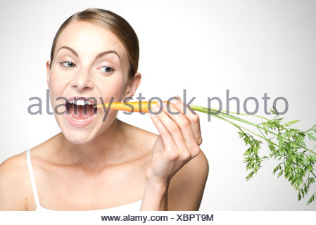 Young woman eating carrot - Stock Photo