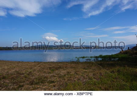 Scenic View Of Lake Against Blue Sky - Stock Photo