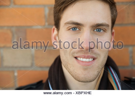 Close-up portrait of smiling man against brick wall - Stock Photo