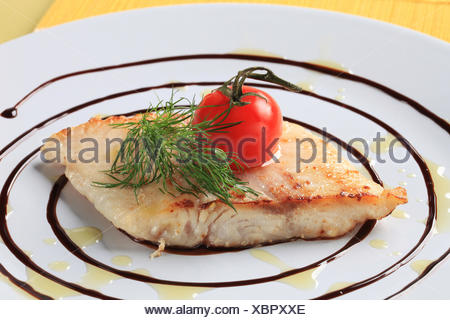 Salmon trout fillet garnished with arugula and balsamic reduction - Stock Photo