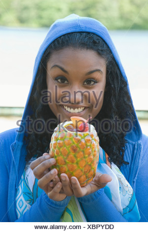 Portrait of a young woman holding a pineapple and smiling - Stock Photo