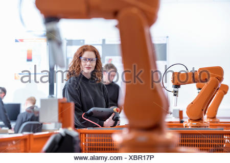 Portrait of female robotics apprentice using test industrial robots in robotics facility - Stock Photo