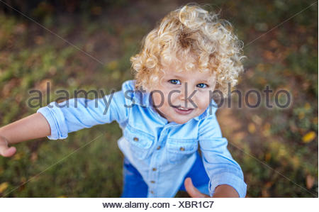 Portrait of smiling blond little boy looking up to camera - Stock Photo