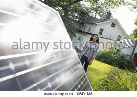 A woman walking towards a solar panel in a farmhouse garden. - Stock Photo