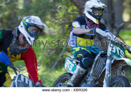 Two young male motocross riders racing through forest - Stock Photo