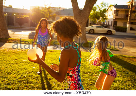 Three girls playing with water balloons in garden - Stock Photo