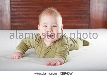 six months age blonde baby green velvet onesie lying on white sheet bed with brown wood background smiling happy face. - Stock Photo