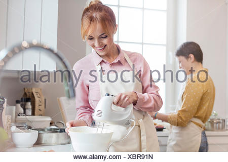 Smiling female caterer baking, using electric hand mixer in kitchen - Stock Photo