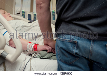 Man holding woman's hand in hospital room - Stock Photo