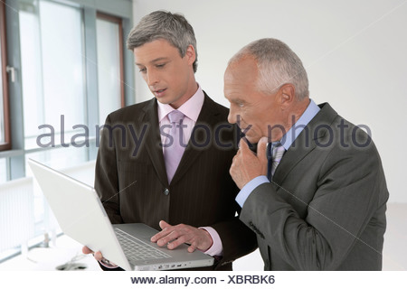 Young businessman working on a laptop, while elderly manager is watching thoughtfully - Stock Photo