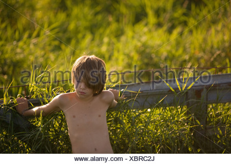 Boy leaning on fence in field - Stock Photo