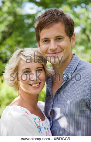 Sweden, Stockholm, portrait of couple embracing outdoors - Stock Photo