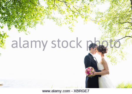 Romantic newlywed mid adult couple kissing in park - Stock Photo