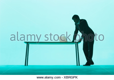 Businessman at a table on a laptop - Stock Photo