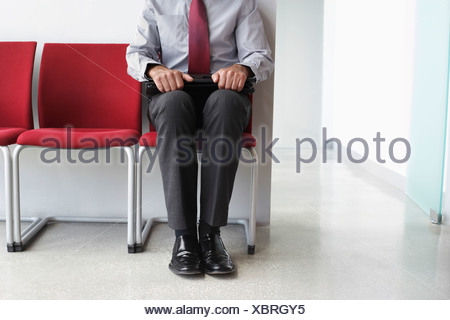 Man waiting on chair in corridor, low section - Stock Photo