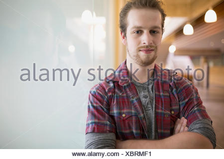 Portrait confident man with arms crossed at frosted glass - Stock Photo