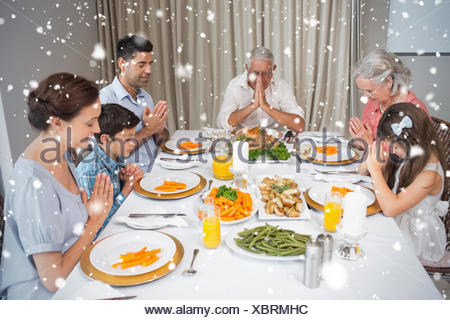 Family of six saying grace before meal at dining table - Stock Photo