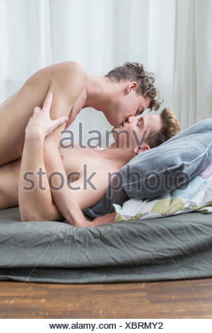 Homosexual couple kssing each other in bed - Stock Photo