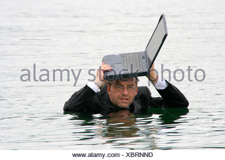 businessman in deep water holdig laptop over his head - Stock Photo