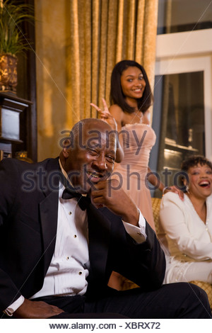 606366cc2c8 ... Teenage girl posing with grandparents in formal attire at home - Stock  Photo