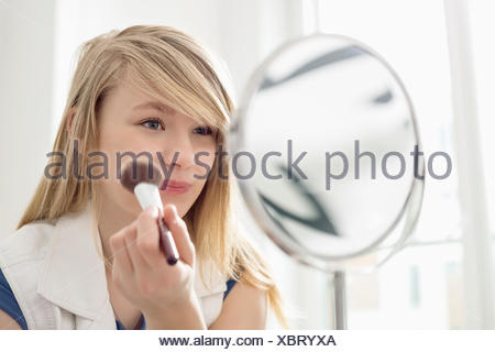 Girl applying makeup in front of mirror at home - Stock Photo