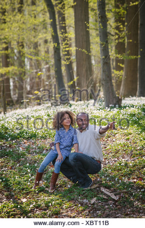 Young girl and father in woods - Stock Photo