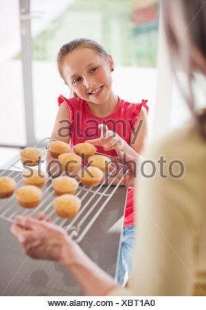 Grandmother offering cupcakes to granddaughter - Stock Photo