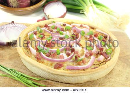 Zwiebelkuchen mit Schinkenspeck vor hellem Hintergrund - Stock Photo