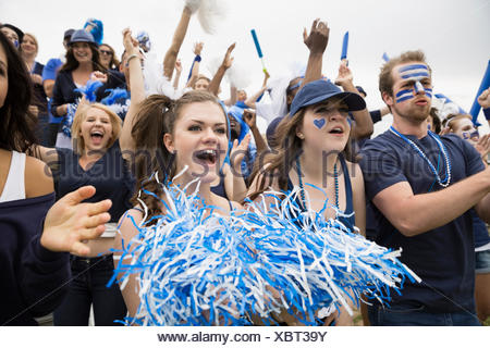 Enthusiastic crowd in blue cheering at sports event - Stock Photo