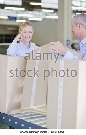 Co-workers standing with boxes on conveyor belt - Stock Photo