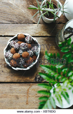 Chocolate truffles covered in nuts, on a wooden table. - Stock Photo