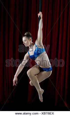 Studio shot of female aerialist performing on rope - Stock Photo