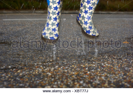 A young child jumping in a puddle wearing Wellington boots - Stock Photo