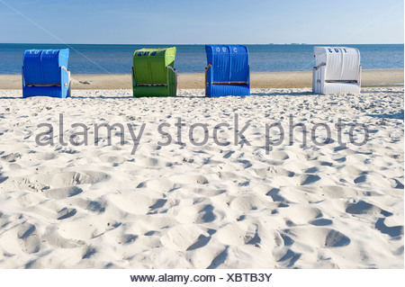 Colourful roofed wicker beach chairs on the beach, Wyk, Foehr, North Frisia, Schleswig-Holstein - Stock Photo