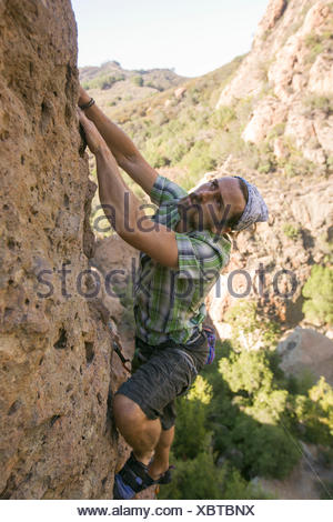 A young man sport climbs at Malibu Creek State Park in southern California. - Stock Photo