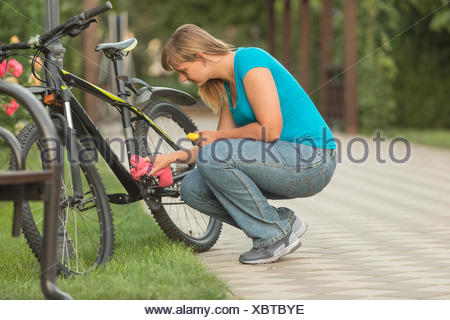 Side view of woman repairing bicycle in park - Stock Photo