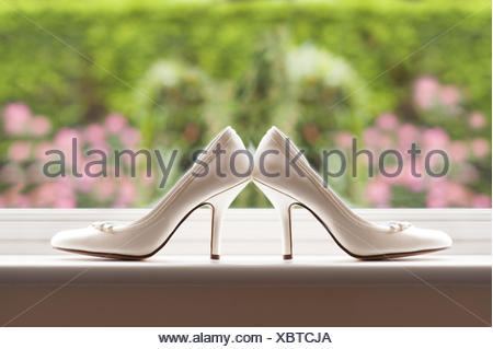 white wedding shoes of the bride by a window - Stock Photo