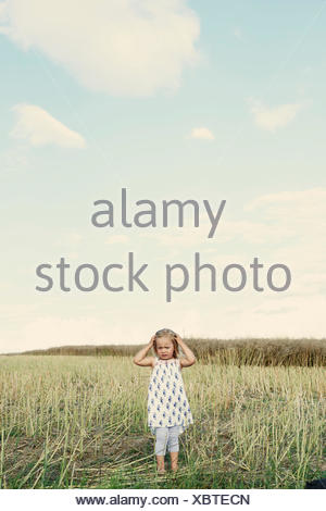 Female toddler standing in wheat field with hand in her hair - Stock Photo