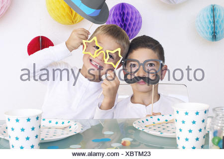 Boys wearing funny disguises at birthday party - Stock Photo