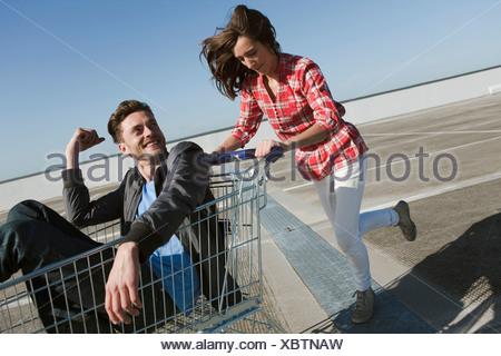 Germany, Berlin, Young woman pushing young man in shopping cart