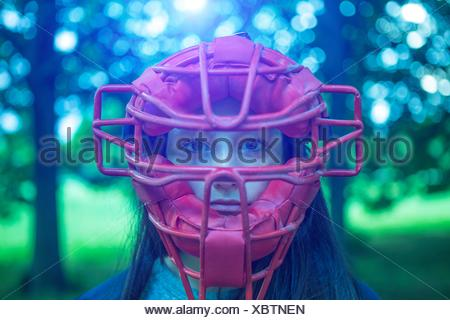 Portrait of staring teenage girl in park wearing red umpire mask - Stock Photo